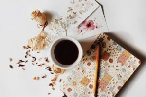 A cup of coffee, a few greeting cards, a few dry flowers, a journal and a pencil.